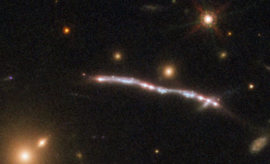 This image, taken with the NASA/ESA Hubble Space Telescope, shows one of four arcs formed of the light from the galaxy nicknamed the Sunburst Arc. Created by strong gravitational lensing, this bright arc of light consists of at least six copies of the image of a single galaxy.