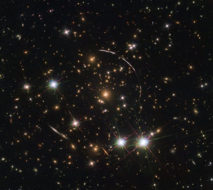 This image, taken with the NASA/ESA Hubble Space Telescope, shows a massive galaxy cluster, about 4.6 billion light years away. Along its borders four bright arcs are visible; these are copies of the same distant galaxy, nicknamed the Sunburst Arc. The Sunburst Arc galaxy is almost 11 billion light-years away and the light from it is being lensed into multiple images by gravitational lensing. The Sunburst Arc is among the brightest lensed galaxies known and its image is visible at least 12 times within the four arcs. Three arcs are visible in the top right of the image, the fourth arc in the lower left. The last one is partially obscured by a bright foreground star, which is located in the Milky Way.