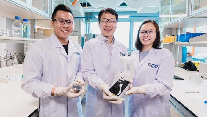 The NUS research team behind the novel algae detection device is led by Assistant Professor Sungwoo Bae (centre) who is holding the smartphone platform. With him are two team members: Mr Si Kuan Thio (left) who is holding the microfluidic chip, and Miss Elaine Chiang (right). Credit: National University of Singapore