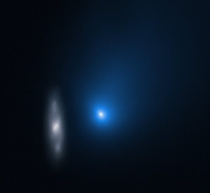 Comet 2I/Borisov is only the second interstellar object known to have passed through our Solar System. In this image taken by the NASA/ESA Hubble Space Telescope, the comet appears in front of a distant background spiral galaxy. The galaxy's bright central core is smeared in the image because Hubble was tracking the comet. Borisov was approximately 326 million kilometres from Earth in this exposure. Its tail of ejected dust streaks off to the upper right.