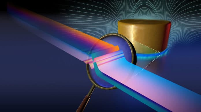 Artistic illustration of nonclassical effects in nanoscale electromagnetism. When the confinement of electromagnetic fields in nanostructures becomes comparable to the electronic length scales in materials, the associated nonclassical effects can substantially affect the electromagnetic response. This illustration represents a film-coupled nanodisk (the nanostructure studied in this work); the insert in the magnifier shows the electronic length scales (in this case, the 'thickness' of the surface induced charge). Credit: Marin Soljači Research Group