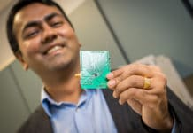 UC San Diego electrical and computer engineering professor Dinesh Bharadia holds a PCB onto which the Wi-Fi radio is mounted.