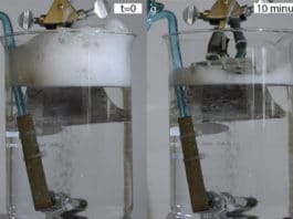 In a beaker with a constant stream of bubbles, inserting a piece of the new textured material developed by the MIT team (gray object extending into the surface at top) causes the foam buildup at the top of the beaker to dissipate almost completely within ten minutes. Courtesy of the Varanasi Lab
