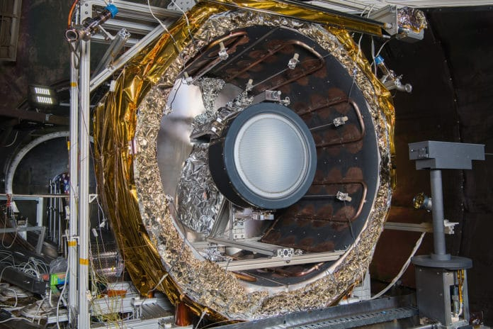The NEXT-C flight thruster is mounted within a thermal shroud in one of NASA Glenn's vacuum chambers.