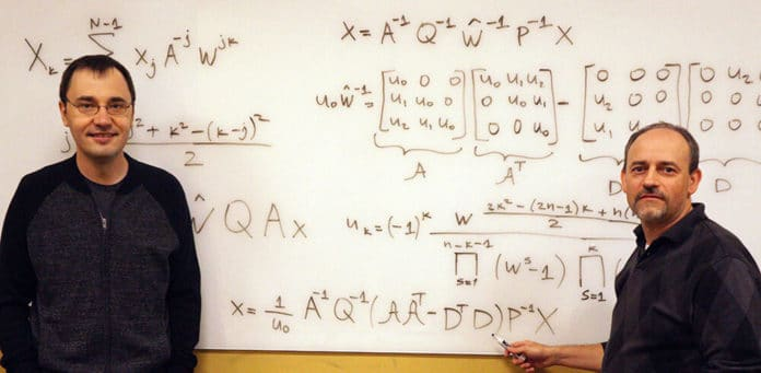Vladimir Sukhoy and Alexander Stoytchev, left to right, with the derivation for the ICZT algorithm in structured matrix notation -- the answer to a 50-year-old puzzle in signal processing. Photo by Paul Easker.