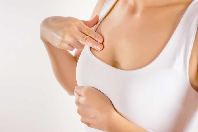 Woman Wearing A White Tank Top Checking Her Breast, Breast Self-Exam (BSE)