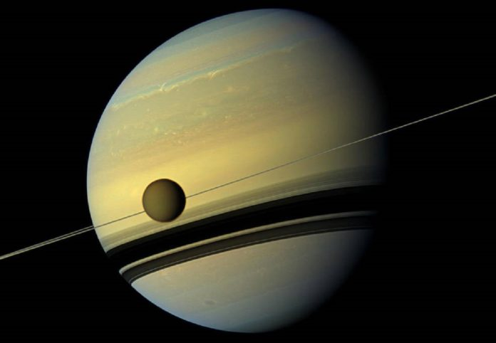 Larger than the planet Mercury, huge moon Titan is seen here as it orbits Saturn. Below Titan are the shadows cast by Saturn's rings. This natural color view was created by combining six images captured by NASA's Cassini spacecraft on May 6, 2012. Credits: NASA/JPL-Caltech/Space Science Institute