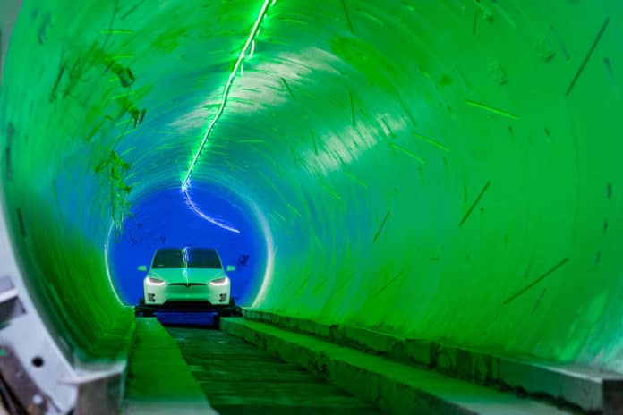 A car is driving through the Boring Company tunnel.