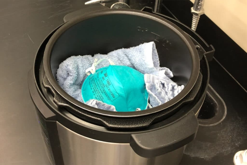 A towel keeps the respirator from touching the heating element on the bottom of the cooker