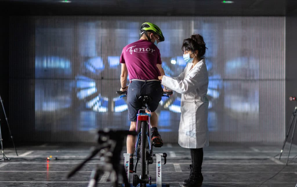 Photo of man on bike and scientist in front of wind tunnel