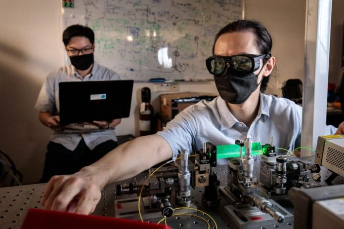 Assistant Professor Charles Lim (back) and Dr Zhang Gong (front) with their team's first-of its-kind quantum power limiter device. Credit: National University of Singapore