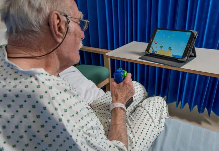 Image showing old man holding rehab device